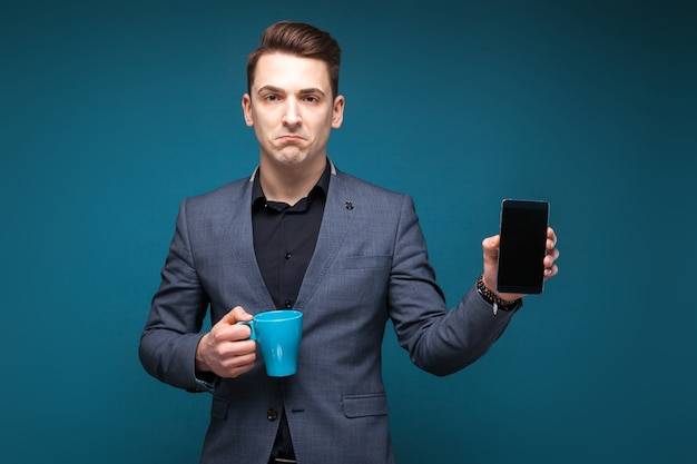 Attractive young businessman in grey jacket and black shirt hold blue cup and show the phone