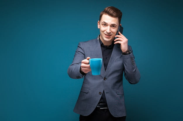 Attractive young businessman in grey jacket and black shirt hold blue cup and talk on the phone