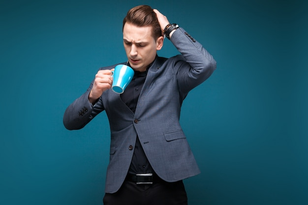 Attractive young businessman in grey jacket and black shirt hold blue cup
