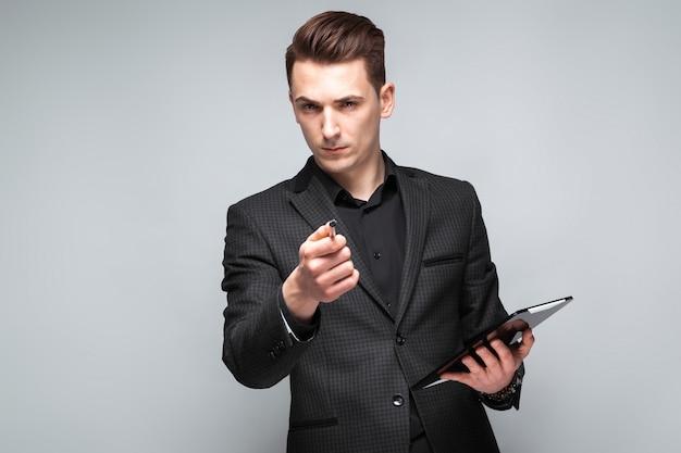 Привлекательный молодой бизнесмен в черный пиджак, дорогие часы и черная рубашка держать планшет
