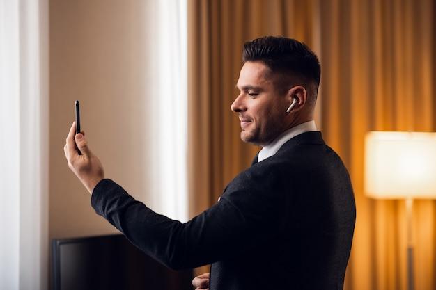 Привлекательный молодой бизнесмен в формальной одежде с видеозвонком на своем смартфоне