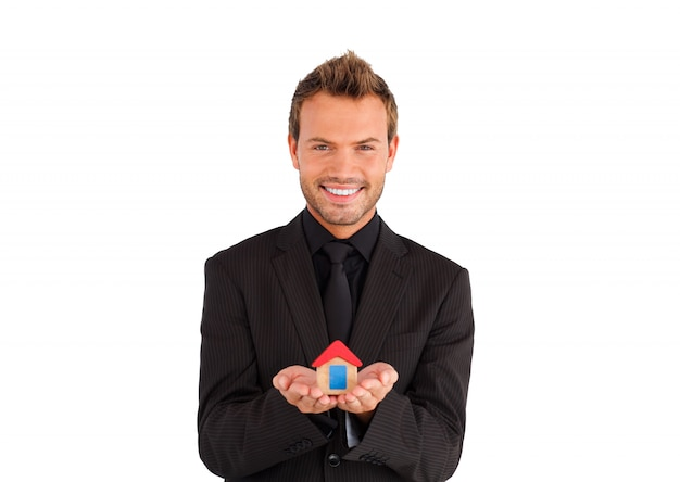 Attractive young businessman presenting a sample of house