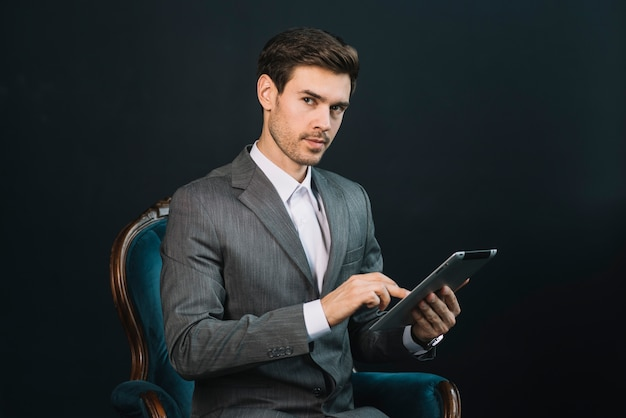 An attractive young businessman sitting in armchair using digital tablet
