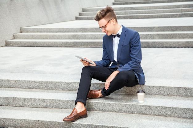魅力的な若いビジネスマンは、オフィスビルの背景にタブレットとコーヒーを手に座っています。タブレットを持って、こぼれるような笑顔でディスプレイを見ています。