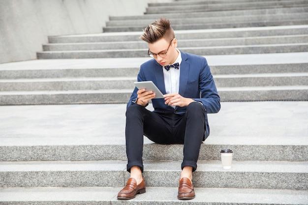 魅力的な若いビジネスマンは、オフィスビルの背景にタブレットとコーヒーを手に座っています。ディスプレイを見ています。