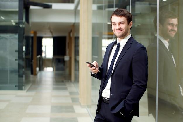 魅力的な青年実業家は近代的なオフィスビルのインテリアでスマートフォンを使用して