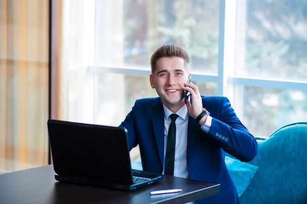 Привлекательный молодой бизнесмен с помощью портативного компьютера во время разговора по мобильному телефону в современном офисе