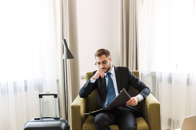 Привлекательный молодой бизнесмен в костюме, сидя в кресле в гостиничном номере, работая с документами
