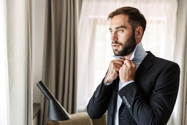 ホテルの部屋に立って、ドレスアップスーツを着て魅力的な青年実業家