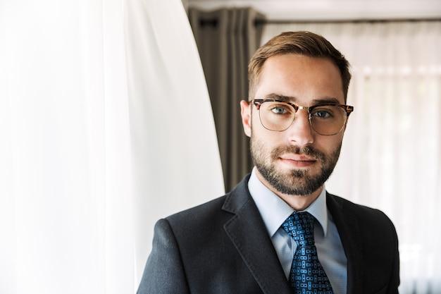Привлекательный молодой бизнесмен в костюме, стоя в гостиничном номере