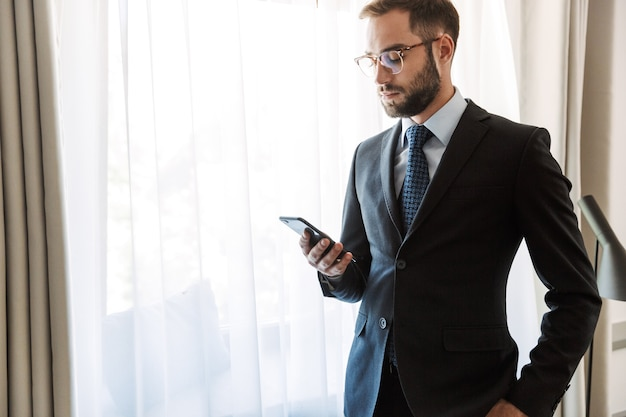 Attractive young businessman wearing suit standing at the hotel room, using mobile phone