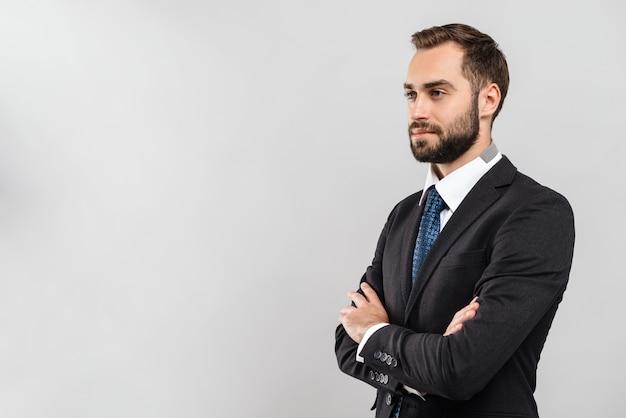 Привлекательный молодой бизнесмен в костюме, стоящий изолированно над серой стеной, скрестив руки на груди