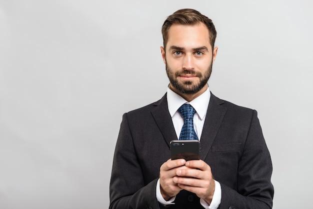 Привлекательный молодой бизнесмен в костюме, стоящий изолированно над серой стеной, держа мобильный телефон