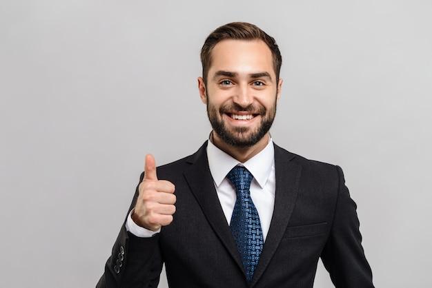 Привлекательный молодой бизнесмен в костюме, стоя изолированном над серой стеной, пальцы вверх