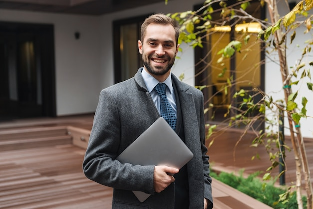 Attractive young businessman wearing suit walking outdoors, carrying laptop computer