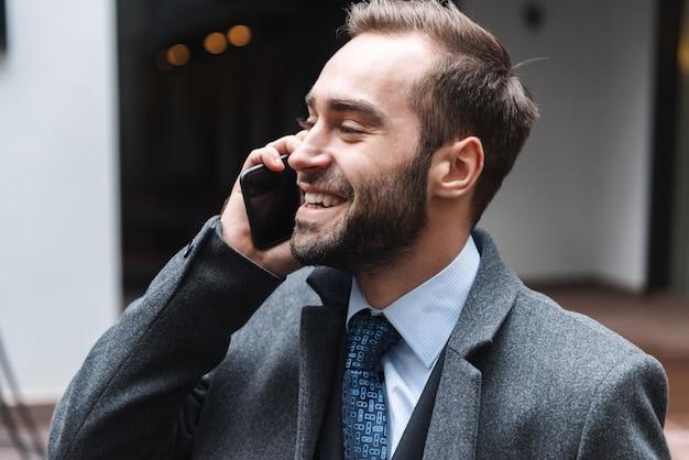 야외에서 걷고, 휴대 전화를 사용하여 양복을 입고 매력적인 젊은 사업가 이야기