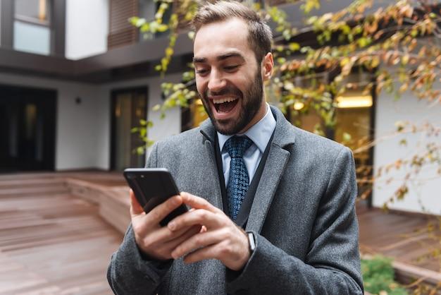 휴대 전화를 사용하여 야외에서 걷고 양복을 입고 매력적인 젊은 사업가