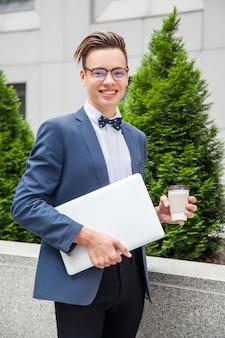 ノートパソコンとコーヒーを手にオフィスビルの背景に魅力的な青年実業家。ラップトップとコーヒーを持って、こぼれるような笑顔でカメラを見ています。
