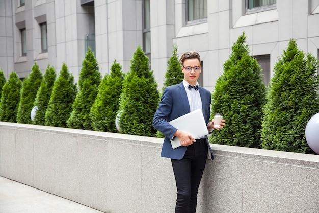 ノートパソコンとコーヒーを手にオフィスビルの背景に魅力的な青年実業家。ラップトップとコーヒーを持ってカメラを見ています。