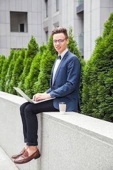 ノートパソコンとコーヒーを手にオフィスビルの背景に魅力的な青年実業家。ラップトップを持って、こぼれるような笑顔でカメラを見ています。