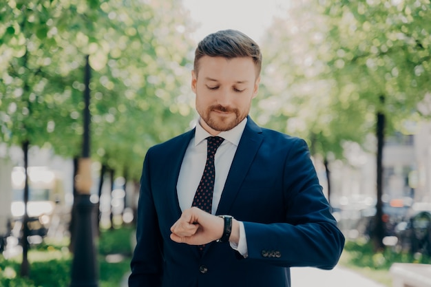 Attractive young businessman with neat trimmed beard in elegant modern suit waiting for meeting date in park outdoor on summer sunny day, impatiently looks at arm watch on his hand