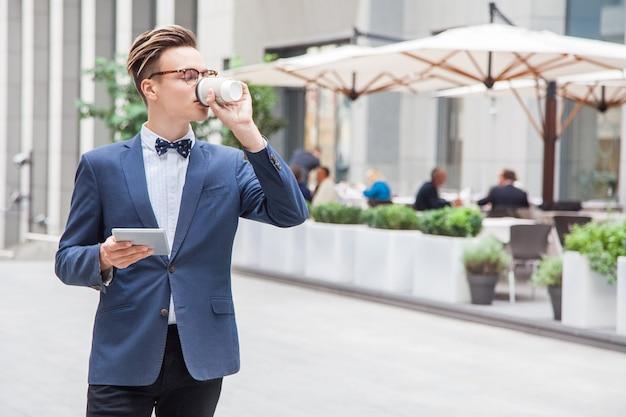 通りのカフェの背景にタブレットとコーヒーを手にした魅力的な青年ビジネスマン。タブレットを持ってコーヒーを飲みます。