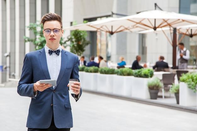通りのカフェの背景にタブレットとコーヒーを手にした魅力的な青年ビジネスマン。笑顔でカメラを見る。