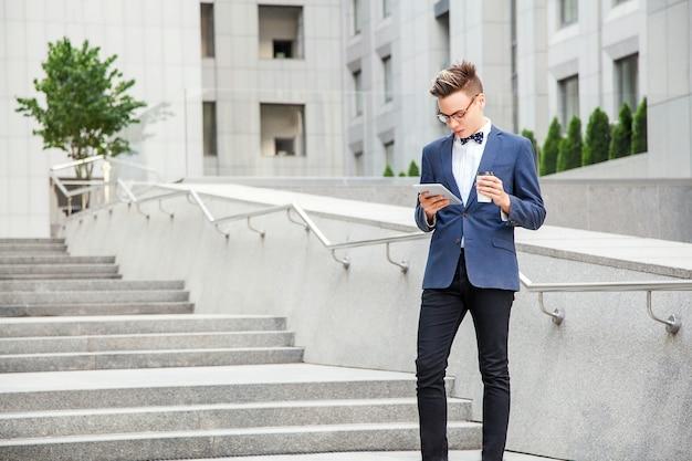 タブレットとコーヒーを手にオフィスビルの背景に魅力的な青年実業家。