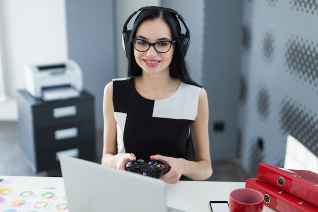 Attractive young businesswoman in black dress, headphones and glasses sit at the table and play on laptop