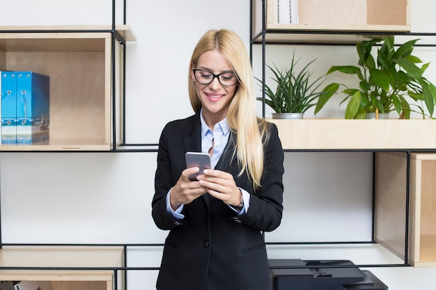 Attractive young businesswoman holding a mobile phone