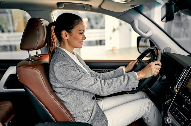Привлекательный молодой предприниматель выбирает новый автомобиль в автосалоне.