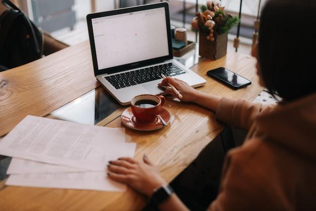 Привлекательный молодой предприниматель печатает на портативном компьютере и работает с бумажным документом