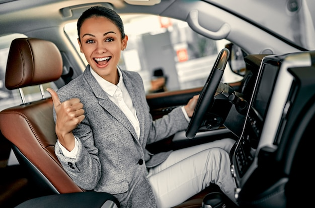 Attractive young businesswoman showing thumbs up is choosing new vehicle in car dealership.
