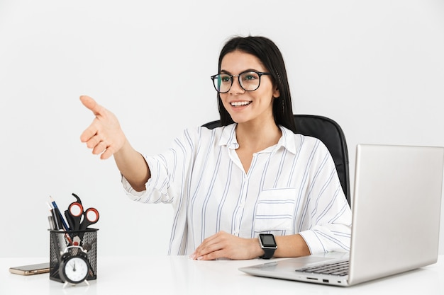 Attractive young businesswoman sitting at the desk isolated over white wall, outstretched hand