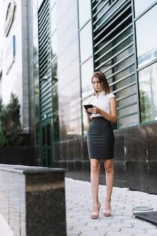 Una giovane donna di affari attraente che per mezzo dello smartphone all'aperto