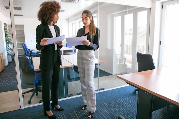 Attractive young businesswomen discussing documentation in hands. two pretty confident female colleagues holding papers and standing in office room. teamwork, business and management concept