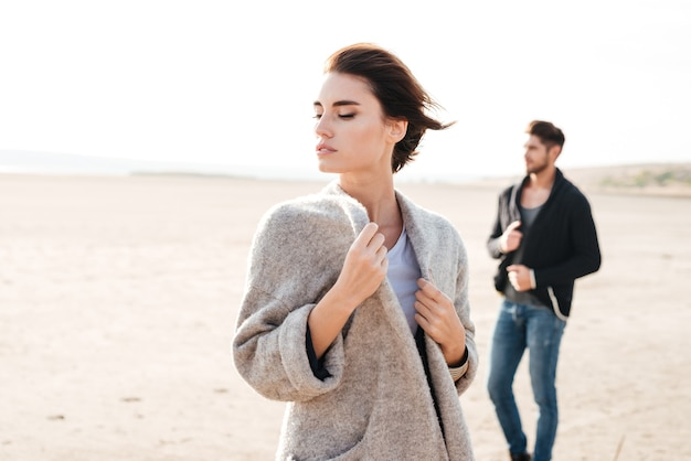 Attractive young casual couple standing at the seashore in the morning