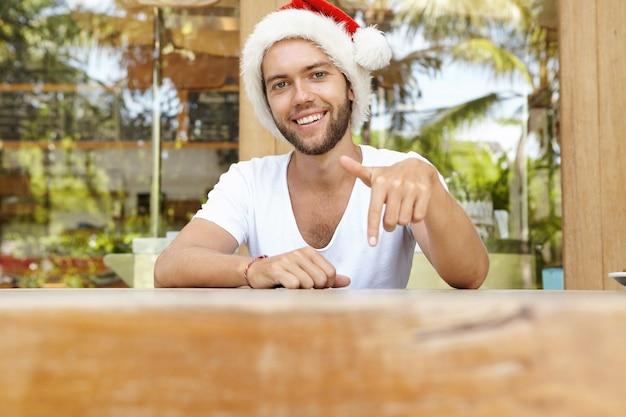 매력적인 젊은 백인 수염 난 남자 흰색 티셔츠와 빨간 산타 클로스 모자 테이블에 앉아 몸짓, 그의 검지 손가락을 아래로 가리키는, 그의 얼굴에 행복하고 쾌활한 표정을 갖는