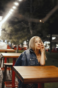 매력적인 젊은 백인 금발 소녀는 야외 테이블 근처에 앉아있다