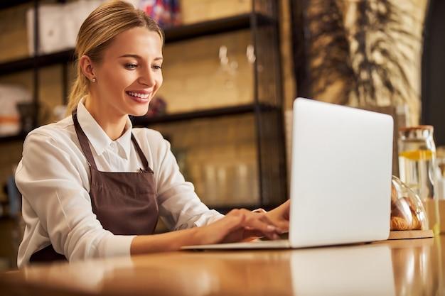 현대적인 장치에서 시간을 보내는 매력적인 젊은 백인 비즈니스 여성
