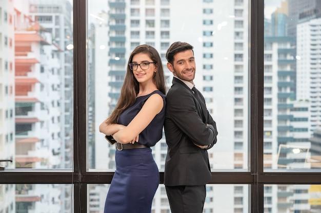 Привлекательный молодой кавказский деловой партнер, стоящий со скрещенными руками, улыбаясь и глядя в камеру в современном офисе в деловом районе