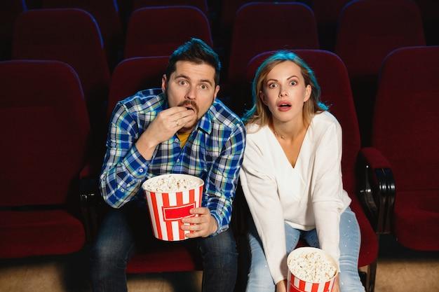 영화 극장, 집 또는 영화관에서 영화를보고 매력적인 젊은 백인 부부. 표현력이 풍부하고 놀랍고 감정적으로 보입니다. 혼자 앉아서 즐겁게 지내기. 관계, 사랑, 가족, 주말 시간.