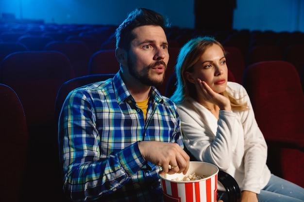 Attraente giovane coppia caucasica guardando un film in un cinema, casa o cinema. guarda espressivo, stupito ed emotivo. seduto da solo e divertendosi. relazione, amore, famiglia, tempo del fine settimana.