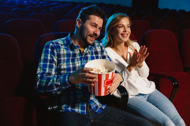 Attractive young caucasian couple watching a film at a movie theater, house or cinema. look expressive, astonished and emotional. sitting alone and having fun. relation, love, family, weekend time.
