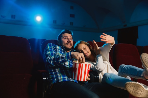 Attraente giovane coppia caucasica guardando un film in un cinema, casa o cinema. guarda espressivo, stupito ed emotivo. seduto da solo e divertendomi. relazione, amore, famiglia, tempo del fine settimana.