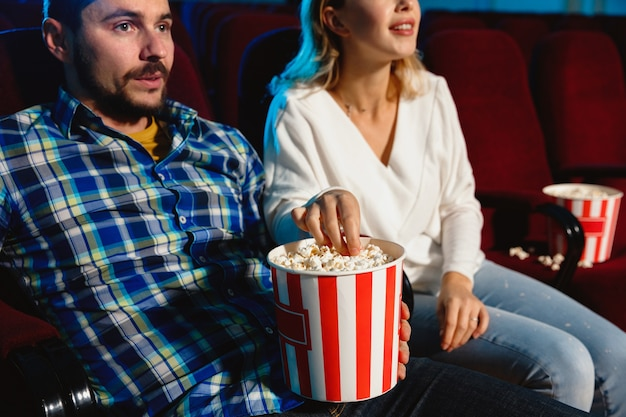 Attractive young caucasian couple watching a film at a movie theater, house or cinema.