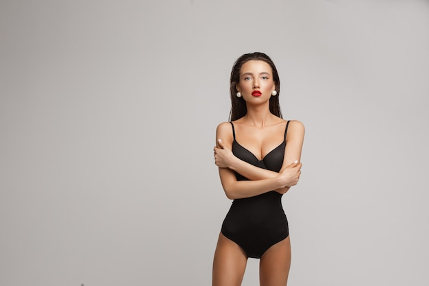 Attractive young caucasian female with long dark hair, nice make up, red lips in black swimsuit crossed her hands on the chest