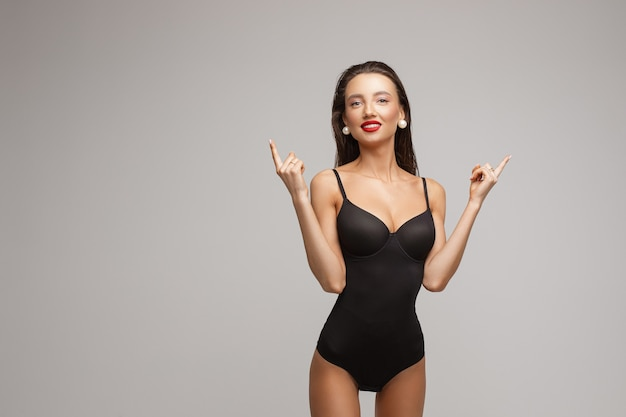 Attractive young caucasian female with long dark hair, nice make up, red lips in black swimsuit smiles