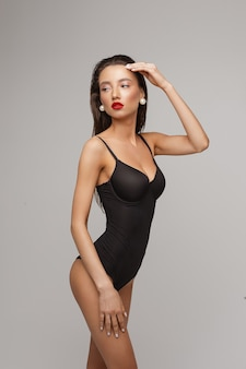 Attractive young caucasian female with long dark hair, nice make up, red lips in black swimsuit touchs her waistline