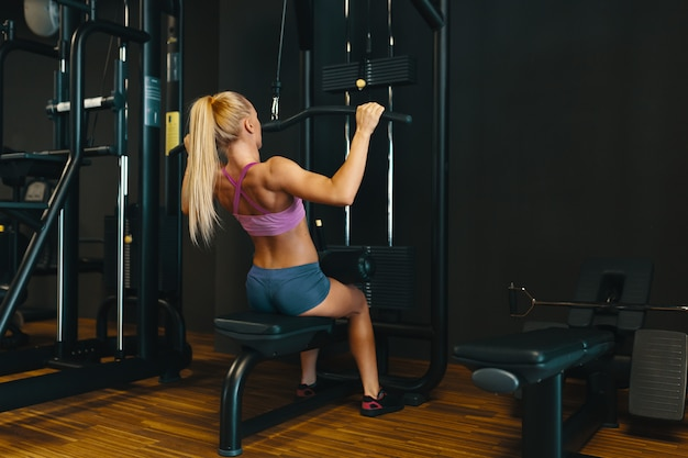 Attractive young caucasian girl in sport wear working out arms a